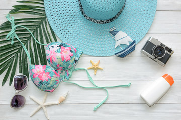 Summer Fashion woman swimsuit Bikini, camera, starfish, sunblock, sun glasses, hat. Travel and vacations in the holiday, wood white background. Summer Concept.