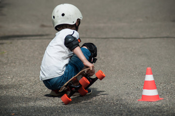 portrait of boy sitting on skate board with helmet