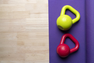 Kettlebell with yoga mat on wooden table, sport and fitness healthy concept