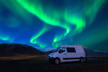 Northern lights (Aurora borealis) and car at night.