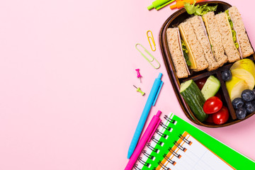 Overhead shoot with wooden lunch box with sandwiches, vegetables and fruits on pink background and school stationery. Healthy children eating concept. Top view with copy space.