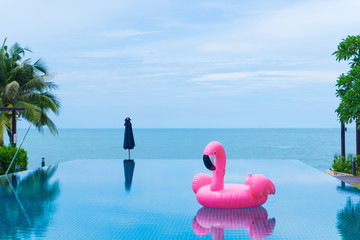 Garden Poster Flamingo flamingo raft floating in swimming pool in front of the sea and island