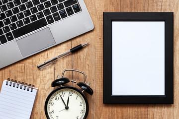Wooden desk with black mockup photo frame, laptop, notebook and black alarm clock