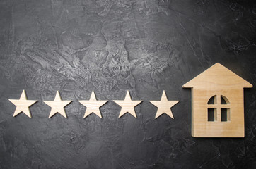 Five stars and a wooden house on a gray concrete background. The concept of the best housing, luxury apartments VIP class. The best service and universal recognition, a high score. Success.