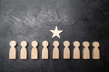 A star above a person who stands in a row among other people. Wooden figurines. The concept of a sign of distinction, success, achievement and career growth. Promotion, the best worker.