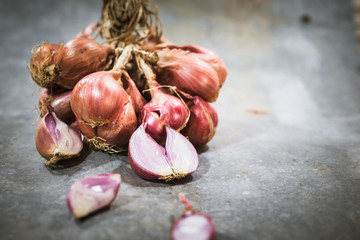 Shallot onions on wooden background, close up view.