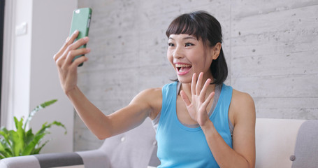 Woman taking selfie on cellphone at home
