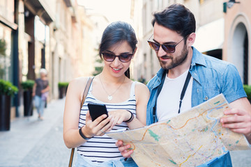 Young happy tourist couple visiting travel destination city with smartphone app