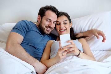 Happy couple wake up and watching mobile phone