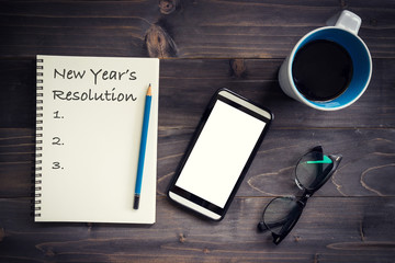 Notebook with 2019 New year's resolution massage with pencil, glasses, phone and cup of coffee on wood background.