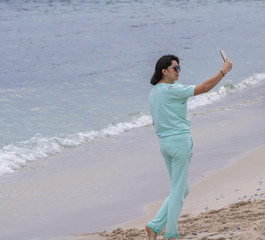 Girl taking fun selfie picture on beach vacation. Summer holiday woman happy at smartphone camera taking self-portrait on her travel vacations in Cannes, France