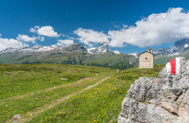 Wall Mural - mountain church in an idyllic mountain landscape in the summertime in the Alps with snow-capped peaks in the background and a hiking trail with marker in the foreground