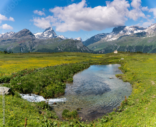 Wall mural idyllic mountain landscape in the summertime with a creek and small pond in the foreground