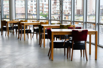 Empty wooden tables and leather chairs stand near the panoramic windows. Food court.