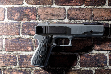 Black & Silver Hand Gun isolated on a brick background