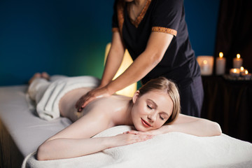 Caucasian woman in wellness beauty spa having aroma therapy massage with essential oil, looking relaxed