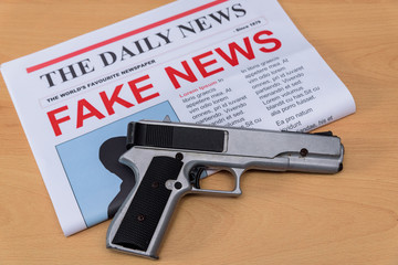 Newspaper with Fake News headline and a nearby Handgun