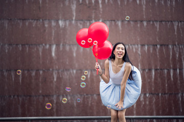 Young Asia woman holding red balloons