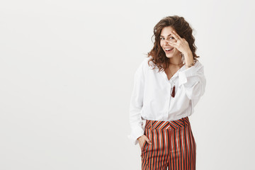 I see everything. Beautiful european woman with curly hair in stylish blouse and striped trousers, peeking through fingers and smiling broadly while gazing at camera, being thrilled and emotive