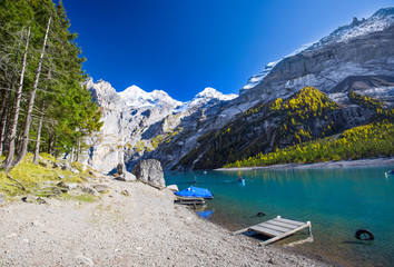 Amazing tourquise Oeschinnensee with waterfalls and Swiss Alps, Berner Oberland, Switzerland