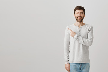 Man recalling something funny. Friendly-looking curious guy with beard pointing left or behind while looking up and planning something with grinning face, posing for advertisement over gray wall