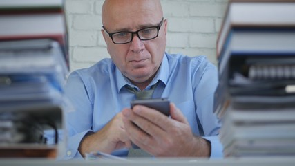 Businessman Wearing Eyeglasses Text Using Cellphone in Office