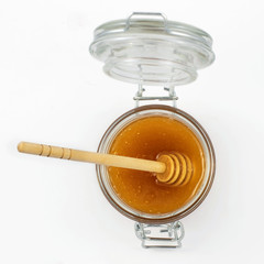 Aromatic honey with dipper into jar isolated on white background. Top view