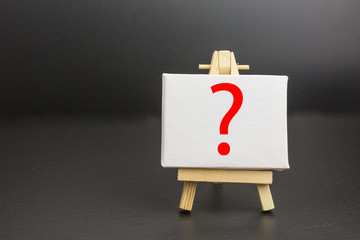 canvas on wooden easel with question mark