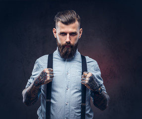 Portrait of a handsome old-fashioned hipster in a blue shirt and suspenders.