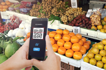 Qr code payment, E wallet , cashless technology concept. Man scaning tag Fresh Fruit in Market accepted generate digital pay without money.
