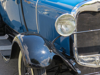 Detail in day of sun, from the classic old car front blue, headlight, radiator and chrome