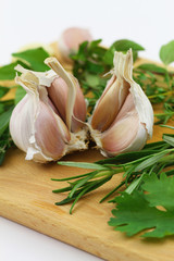 Closeup of garlic cloves and fresh herbs on wooden board
