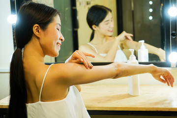 Young Asian girl in spaghetti strap tank top applying sunscreen lotion all over body.