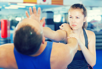 Woman and trainer practicing punches in gym