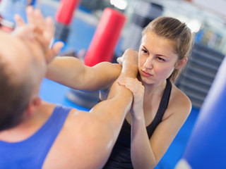Young female and trainer are training kick  in gym