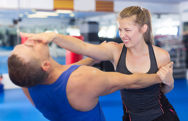 Smiling woman is fighting with trainer