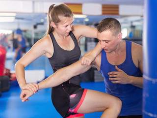 Young active woman exercise fight with man trainer