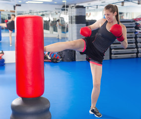 Young female boxer training with punching bag