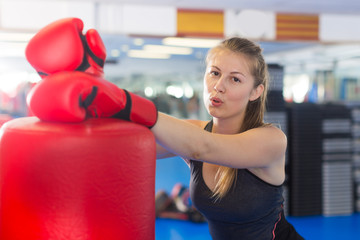 Portrait of active female with  punching bag