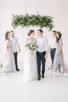 Newly married couple with groomsmen and bridesmaids posing on wedding ceremony