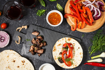 Fresh delicious mexican tacos and food ingredients on black stone background. Cooking.
