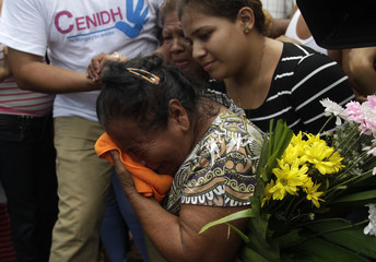 Relative mourns during funeral for a person who died after a building caught fire in Managua