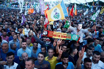 A supporter of Turkey's main pro-Kurdish Peoples' Democratic Party wears a mask of their jailed former leader and presidential candidate Selahattin Demirtas during a campaign event in Istanbul