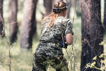Girl in camouflage with a gun, plays laser tag in the forest. the player is aiming. Lasertag shooting game in open air. Military sport. Simulation of military operations. blur