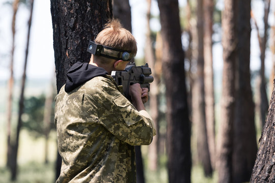 Young boy in camouflage with a gun, plays laser tag in the forest. the guy is aiming. Lasertag shooting game in open air. Military sport. Simulation of military operations