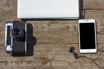 camera phone and laptop are on a wooden table