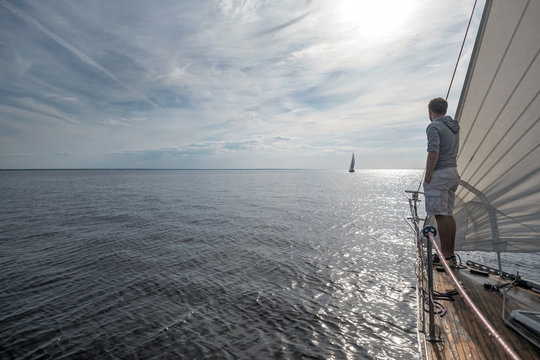 young european man standing at edge of yacht looking at sea.