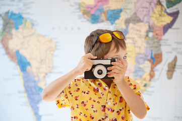 cute young kid photographer taking picture with vintage film camera world map