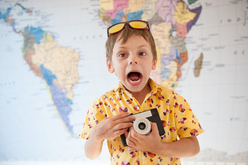 funny shouting little kid in yellow shirt with vintage camera in hands world map