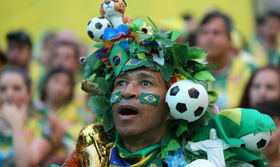 A fan watches the broadcast of the FIFA World Cup Group E soccer match between Brazil and Switzerland, in Rio de Janeiro